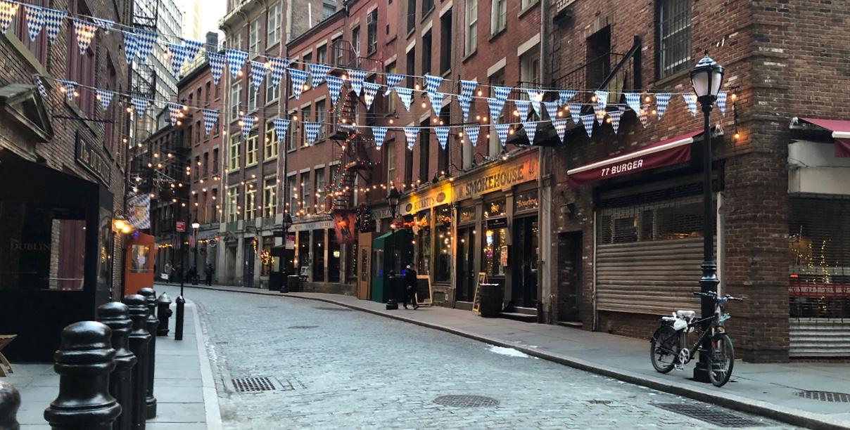 A photo of a warmly-lit brick-cobbled street