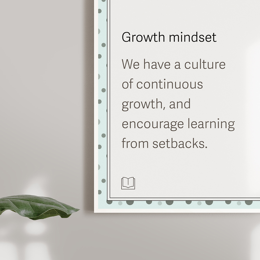 A close-up photograph of a poster on a wall that reads 'Growth Mindset: We have a culture of continuous growth, and encourage learning from setbacks.'
