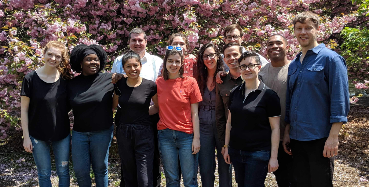 A group photo of Quill employees posing in front of a blossoming cherry tree