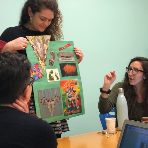 A photograph of a Quill employee presenting a collage to fellow employees